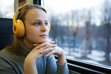 Woman traveling by train with favorite music