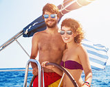Joyful couple driving sailboat