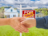 Shaking Hands in Front of New House and Sold Sign