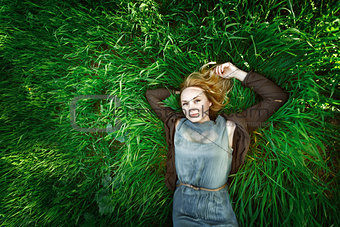 Beautiful meditative young woman lying in the grass. Summer, fre