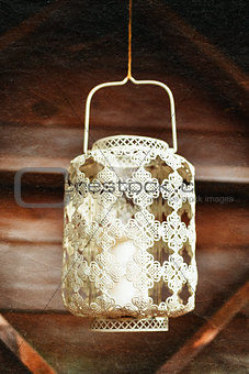 Old-fashioned lacy white lantern. Textured background.