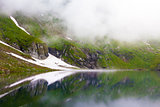 Idyllic view with snow on Balea Lake shore in Fagaras Mountains