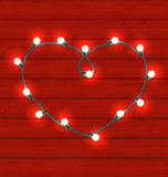Garland heart shaped on red wooden background for Valentines Day