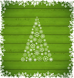 Christmas pine and border made of snowflakes on green wooden ba