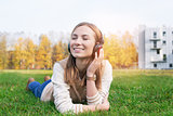 Student lying on grass and listening music into headphones