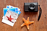 retro camera, starfish and some photos on a wooden surface