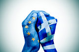 hands patterned with the European and the Greek flag put togethe