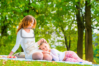 beautiful girl stroking her daughter on the lawn in the park