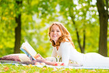 laughing girl with a good book on the grass in the summer park