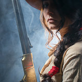 girl cowboy with  gun on a gray background