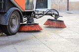 Vehicle sweeping the streets of dirt.
