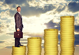 Businessman standing on coins steps