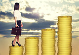Businesswoman standing on coins steps