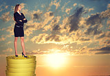 Businesswoman standing on coins stack