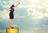 Businesswoman standing on coins stack in balance
