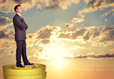 Thoughtful businessman standing on coins stack