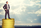 Businessman standing on coins stack