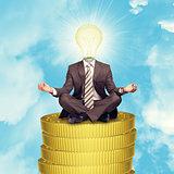 Sitting businessman on coins step