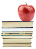 Fresh apple on pile of books