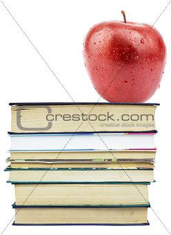 Fresh apple on pile of books