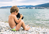Little photographer with big camera on beach near sea