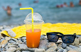 Juice with drinking straw and sunglasses on beach near sea