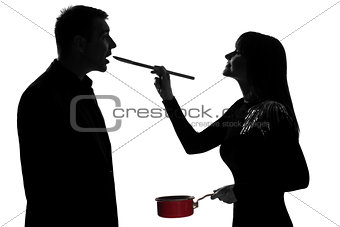 one couple man and woman tasting cooking sauce pan silhouette
