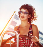 Beautiful woman driving sailboat