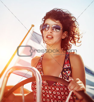 Beautiful woman driving sailboat