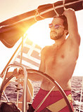 Handsome guy driving sailboat