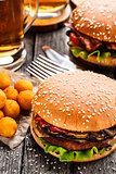 Delicious burger with fried potato balls and beer