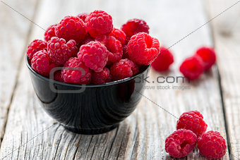 Bowl with ripe raspberry.