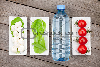 Tomatoes, mozzarella, green salad leaves and water bottle