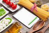 Tomatoes, mozzarella, pasta and green salad leaves with notepad