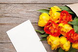Colorful tulips and greeting card on wooden table