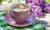 Coffee cup and colorful lilac flowers