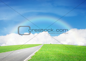 Asphalt road through the green field and sky with clouds and rai
