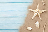 Sea sand with starfish and shells on wood