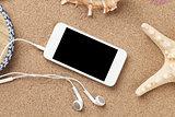 Smartphone on sea sand with starfish and shells