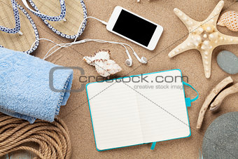 Smartphone and notepad on sea sand with starfish and shells