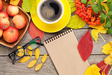Autumn leaves, apple fruits, coffee cup and notepad