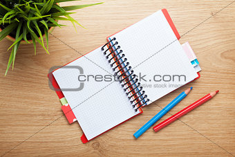 Office table with flower, blank notepad and colorful pencils