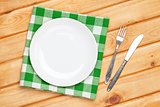 Empty plate, silverware and towel over wooden table background