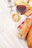 White and red wine, cheese and bread on white wooden table backg