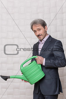 Mature businessman with watering pot