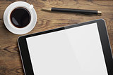 Tablet pc on table desk with coffee cup and pen