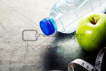 Green apple, water and measuring tape. Health and diet concept