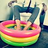man in suit soaking his feet in an inflatable water pool, with a