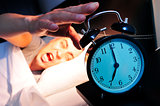 young man in bed stopping the alarm clock