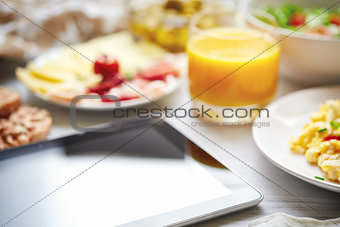 Fresh continental breakfast. Tablet, black screen, selective foc